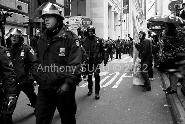"""New York, New York<br /> November 17, 2011<br /> <br /> """"Occupy Wall Street"""" protesters mark the movement's two-month milestone by marching from Zuccotti Park, in mass, to various access streets surrounding the New York Stock Exchange, which the police had barricaded off. Yet instead of the police keeping protesters out, protesters locked down those entrances to Wall Street and the New York Stock Exchange creating havoc as the police made more then 240 arrests to try and keep the streets open to normal traffic.<br /> <br /> At Williams and Pine street, NYPD arrest dozens of protesters,  including a woman in a wheelchair. The anti-Wall Street protesters intention to disrupting business as usual on Wall Street was successful."""