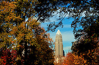 An autumn scene in Charlotte, North Carolina. Bank of America tower in framed by tree branches and colorful autumn leaves.