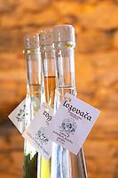 Bottles of rakija grappa type spirit clear and with herbs. Triangular conic bottles with light shining through. Translucent. Lozovaca. Toreta Vinarija Winery in Smokvica village on Korcula island. Vinarija Toreta Winery, Smokvica town. Peljesac peninsula. Dalmatian Coast, Croatia, Europe.