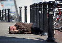 Pictured: A homeless man sleeps on the ground outside the National Stadium of Wales (aka Principality Stadium) Thursday 25 May 2017<br />