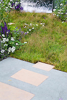 Meadow grass planting next to sleek patio, with flowers and water feature waterfall