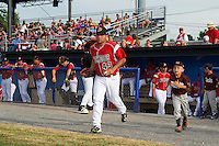 """Batavia Muckdogs first baseman Eric Gutierrez (43) takes the field with a young """"Stars of the Game"""" participant before a game against the Brooklyn Cyclones on July 4, 2016 at Dwyer Stadium in Batavia, New York.  Brooklyn defeated Batavia 5-1.  (Mike Janes/Four Seam Images)"""