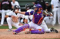 Catcher Chris Williams (27) of the Clemson Tigers displays the ball as he tags runner Jacob Olsen (7) out at the plate in the bottom of the ninth, preserving an 8-7 win over the South Carolina Gamecocks on Saturday, March 4, 2017, at Fluor Field at the West End in Greenville, South Carolina. Clemson won, 8-7. (Tom Priddy/Four Seam Images)