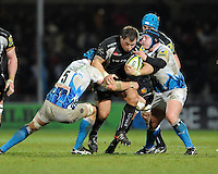 Ben Moon of Exeter Chiefs (centre) is tackled by Ben Skirving (left) and Pieter Dixon of Bath Rugby during the LV= Cup match between Exeter Chiefs and Bath Rugby at Sandy Park Stadium on Sunday 5th February 2012 (Photo by Rob Munro)