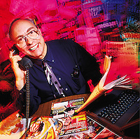 Smiling portrait of busy-looking man on telephone, with magazines, newspaper and laptop computer around him.