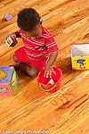 13 month old baby boy dopping toy block into bucket