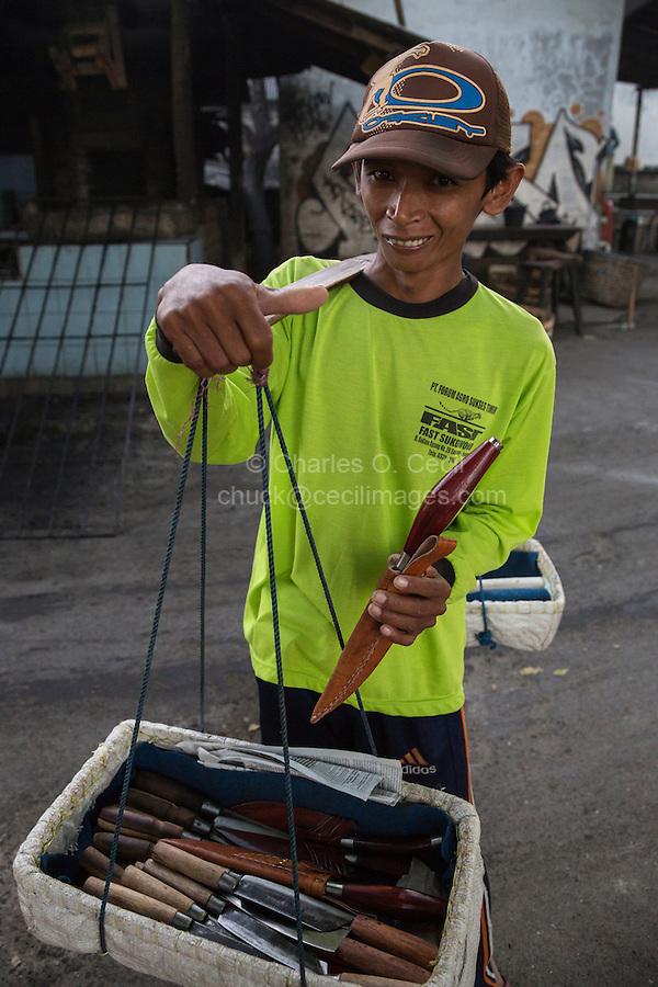 Bali, Indonesia.  Young Street Vendor Selling Knives and Sheaths, outside Jimbaran Market.