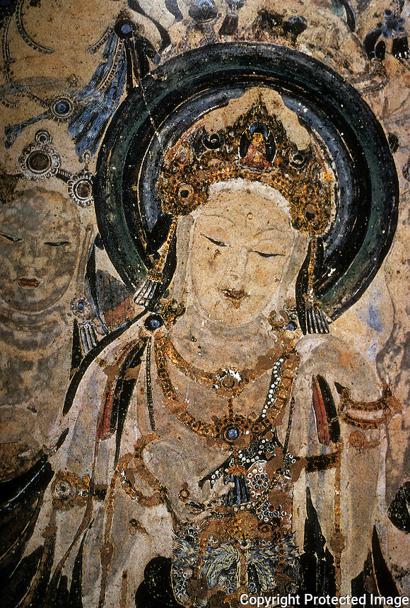 """Chinese Buddhist Art:  """"Bodhisativa"""",  Early Tang (7th C.)  This Bodhisativa attendant stands to the right of Buddha in a cave mural. """"she""""-for it must be a  she--wears an especially ornate coronet the peak of which shows a small buddha.  CHINESE PAINTING, Torao Miyagamwa, 1985."""