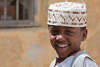 Zanzibar, Tanzania.  Young Boy Wearing a Traditional Hat, a Kofia, in Stone Town.