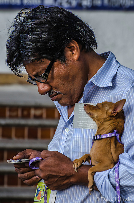 Urban Street Photograph of a Mexican man with his Chihuahua under his arms.
