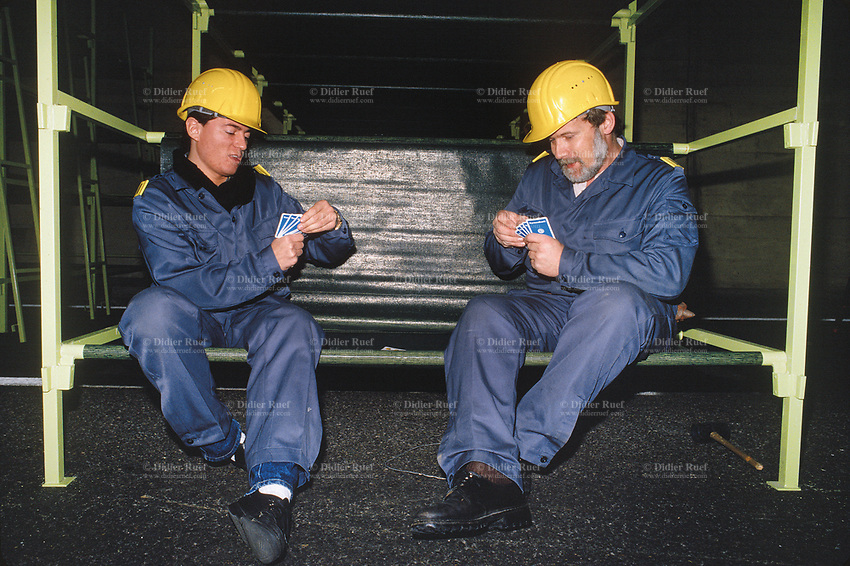 Switzerland. Canton Lucerne. Two men with yellow helmets play cards seated on bunk beds in the Sonnenberg tunnel in Lucerne during the largest civil defense exercise ever held in the country. From 16 to 21 November 1987, almost 1200 men and women converted a motorway tunnel into perhaps the world's largest bunker structure. The civil protectors had to prove during the exercise «Ameise» ( Ants in english) that in an emergency more than 20,000 inhabitants of the city of Lucerne could survive here in the mountain for two weeks. The Sonnenberg Tunnel is a 1,550m  long motorway tunnel, constructed between 1971 and 1976. At its completion it was also the world's largest civilian nuclear fallout shelter, designed to protect 20,000 civilians in the eventuality of war or disaster. Based on a federal law from 1963, Switzerland aims to provide nuclear fallout shelters for the entire population of the country. The construction of a new tunnel near an urban centre was seen as an opportunity to provide shelter space for a large number of people at the same time. The giant bunker was built between 1970 and 1976 at a cost of 40 million Swiss francs. The shelter consisted of the two motorway tunnels (one per direction of travel), each capable of holding 10,000 people in 64 person subdivisions. A seven story cavern between the tunnels contained shelter infrastructure including a command post, an emergency hospital, a radio studio, a telephone centre, prison cells and ventilation machines. The shelter was designed to withstand the blast from a 1 megaton nuclear explosion 1 kilometer away. The blast doors at the tunnel portals are 1.5 meters thick and weigh 350 tons. The logistical problems of maintaining a population of 20,000 in close confines were not thoroughly explored, and testing the installation was difficult because it required closing the motorway and rerouting the usual traffic. The only large-scale test, a five-day exercise in 1987 to practice converting the road tunn