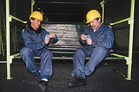 Switzerland. Canton Lucerne. Two men with yellow helmets play cards seated on bunk beds in the Sonnenberg tunnel in Lucerne during the largest civil defense exercise ever held in the country. From 16 to 21 November 1987, almost 1200 men and women converted a motorway tunnel into perhaps the world's largest bunker structure. The civil protectors had to prove during the exercise «Ameise » ( Ants in english) that in an emergency more than 20,000 inhabitants of the city of Lucerne could survive here in the mountain for two weeks. The Sonnenberg Tunnel is a 1,550 m  long motorway tunnel, constructed between 1971 and 1976. At its completion it was also the world's largest civilian nuclear fallout shelter, designed to protect 20,000 civilians in the eventuality of war or disaster. Based on a federal law from 1963, Switzerland aims to provide nuclear fallout shelters for the entire population of the country. The construction of a new tunnel near an urban centre was seen as an opportunity to provide shelter space for a large number of people at the same time. The giant bunker was built between 1970 and 1976 at a cost of 40 million Swiss francs. The shelter consisted of the two motorway tunnels (one per direction of travel), each capable of holding 10,000 people in 64 person subdivisions. A seven story cavern between the tunnels contained shelter infrastructure including a command post, an emergency hospital, a radio studio, a telephone centre, prison cells and ventilation machines. The shelter was designed to withstand the blast from a 1 megaton nuclear explosion 1 kilometer away. The blast doors at the tunnel portals are 1.5 meters thick and weigh 350 tons. The logistical problems of maintaining a population of 20,000 in close confines were not thoroughly explored, and testing the installation was difficult because it required closing the motorway and rerouting the usual traffic. The only large-scale test, a five-day exercise in 1987 to practice converting the road tunn