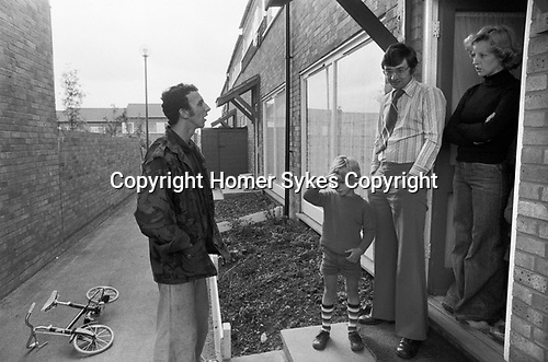 1970s family, middle income professional couple, mother, father and child, they have come to the front door to chat to a neighbour. Standing on the front door step. 1977 Modern housing development in new town England 1977  Milton Keynes Buckinghamshire.