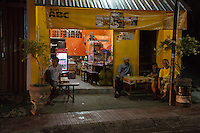 Bali, Indonesia.  Men at a Sidewalk Refreshment  Stand at Night.  Klungkung, Semarapura.