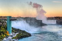 Soft light from the rising sun reflects off the spray from Horseshoe Falls with the American Falls on the left just after sunrise in Niagara Falls.