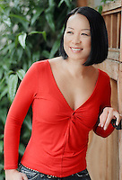 Attractive Asian woman leans on garden gate..MR