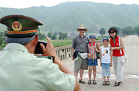 01-AUG-02: NORTH KOREAN BORDER: TUMEN, JILIN, CHINA<br /> Surreal normality on the North Korean border as a People's Liberation Army border guard photographs a South Korean family of tourists at the Tumen Bridge border crossing where refugees are sent back to the North.