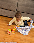 10 month old baby boy pulling cloth off hidden toy, finding hidden toy Piaget object permanence