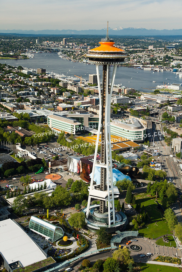 top of Space Needle painted orange for its 50th Anniversary celebration with Bill & Melinda Gates Foundation campus and Lake Union behind; Seattle, WA