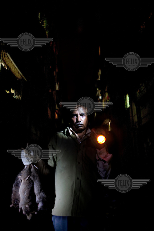 56 year old Jahid Sheikh on a street carrying dead rats he has just caught. He has been a rat catcher in the Mumbai suburbs for twenty years.