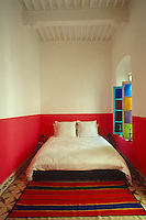 This bedroom has been painted red and white accented with a red striped rug on the tiled floor