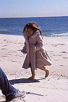Girl in pink coat runnung on beach<br />
