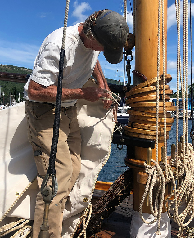 Traditional skills, traditional materials. Ron Hawkins fitting the classic cotton mainsail to mast-hoops he made himself. Note the complete set of traditional bronze belaying pins