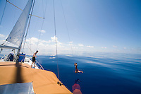 Crew of a cruising sailboat swinging by the halyards in the windless Pacific High, during a Pacific crossing