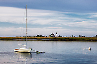 Boat anchored by Stage Harbor Lighthouse at Harding Beach, Chatham, Cape Cod, Massachusetts, USA.