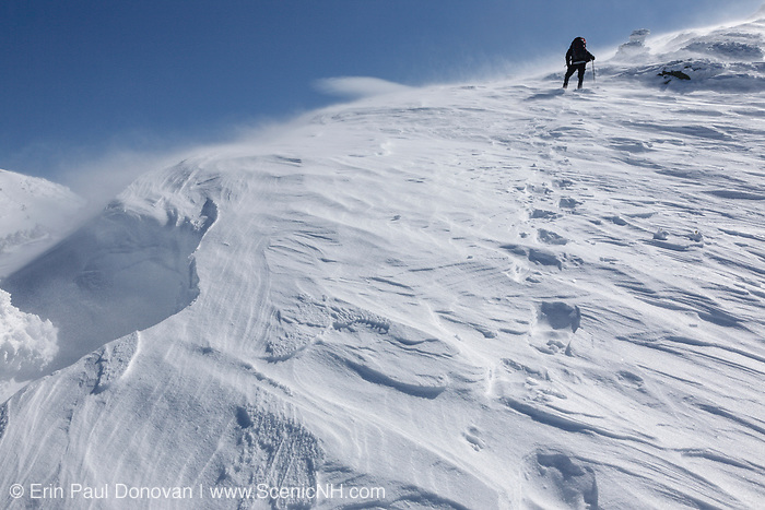 A winter hiker ascending the Air Line Trail in the White Mountains, New Hampshire during the winter months. This trail is a popular route to Mount Adams.
