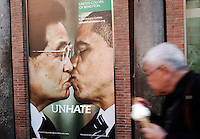 Un fotomontaggio raffigurante il presidente cinese Hu Jintao, a sinistra, che bacia sulla bocca il presidente degli Stati Uniti Barack Obama, parte di una campagna pubblicitaria della Benetton, in uno dei suoi negozi a Roma, 17 novembre 2011..A man passes past a photo montage of a new ad campaign of Italian clothing company Benetton, showing US president Barack Obama, right, and Chinese president Hu Jintao kissing each other on the lips, in a Benetton shop in Rome, 17 November 2011..UPDATE IMAGES PRESS/Riccardo De Luca