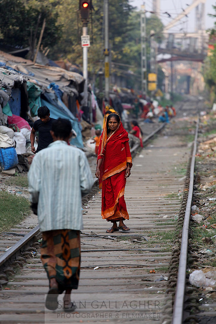 A woman walks along train tracks in central Kolkata.<br />