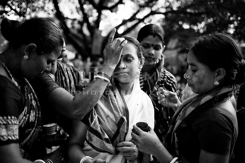 """During Kartik, """"the holiest month"""" beginning every year with the new moon in November, thousands of Hindu devotees celebrate the feast of Rakher Upobash, fasting and praying the gods sitting before the Shri Shri Lokanath Brahmachari Ashram, among the Swami Bagh Temple near Dhaka, Bangladesh. The worshippers offer candles called Prodip, meditate, give to charity, and generally perform austerity. Devotees women prepare for the celebration. Barodi, Dhaka, Bangladesh. Nov. 08, 2014"""