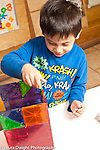 Education Preschool  3 year old boy building with colorful magnetic plastic tiles