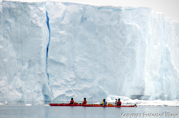 Kayakers exploring an Iceberg on the cold waters of antarctica