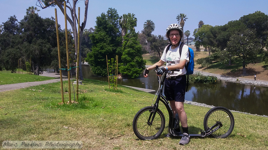 """Holland poses with his Yedoo Dragstr aluminum-frame, 20"""" wheel kick scooter in Hollenbeck Park during the 2017 (17th annual) Los Angeles River Ride.  Holland's customized higher-than-normal handlebars and the water bottle attachment can be seen.  Palm and other trees can be seen around the lake in the background."""