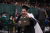Tran Phu, B.B.A. Management, celebrates after receiving his degree during UAA's 2019 Spring Commencement at the Alaska Airlines Center.