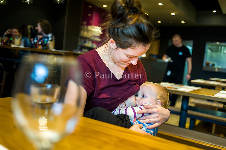 A mother breastfeeding her 10 month old son in a restaurant. The waiter is bringing the bill.<br /> <br /> Herefordshire, England, UK<br /> 09/01/2015<br /> <br /> © Paul Carter / wdiip.co.uk