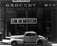 "San Francisco, Calif., Mar. 1942. A large sign reading ""I am an American"" placed in the window of a store, at 13th and Franklin streets, on December 8, the day after Pearl Harbor. The store was closed following orders to persons of Japanese descent to evacuate from certain West Coast areas. The owner, a University of California graduate, will be housed with hundreds of evacuees in War Relocation Authority centers for the duration of the war"