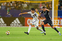 CARSON, CA - SEPTEMBER 15: Joe Corona #14 of the Los Angeles Galaxy moves with the ball past Roger Espinoza #17 of Sporting Kansas City during a game between Sporting Kansas City and Los Angeles Galaxy at Dignity Health Sports Park on September 15, 2019 in Carson, California.