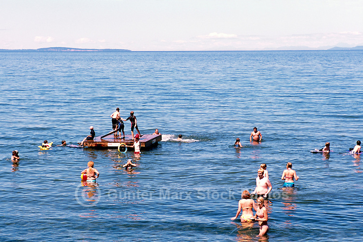 "People wading and swimming in the Pacific Ocean at Qualicum Beach, in the ""Oceanside Region"" of Vancouver Island, British Columbia, Canada"