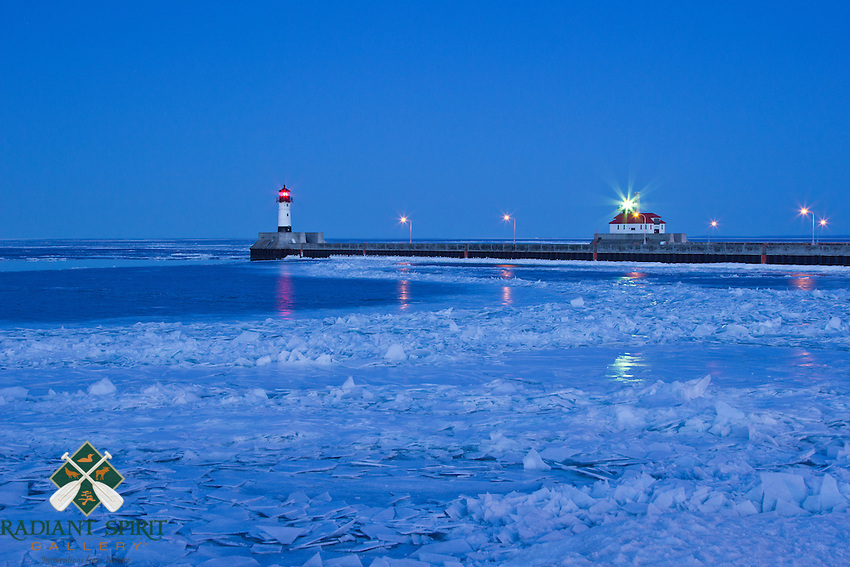 """""""Winter Twilight in Canal Park""""<br /> The lighthouses in Duluth's canal cast their twilight glow on the frosted ice shards of Lake Superior's shoreline."""