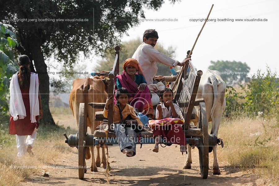 INDIA, Madhya Pradesh, Nimad region, Khargone , tribal farmer of cooperative Shiv Krishi Utthan Sanstha, family travels with bullock cart / INDIEN, Madhya Pradesh, Khargone, Adivasi farmer der Kooperative Shiv Krishi Utthan Sanstha, Familie auf einem Ochsenkarren