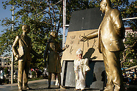 Turkish boy in his circumcision outfit posing in front of a statue of Ataturk teaching the Latin alphabet