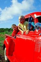Children enjoy a ride in the country in Dad's old red Ford Pickup