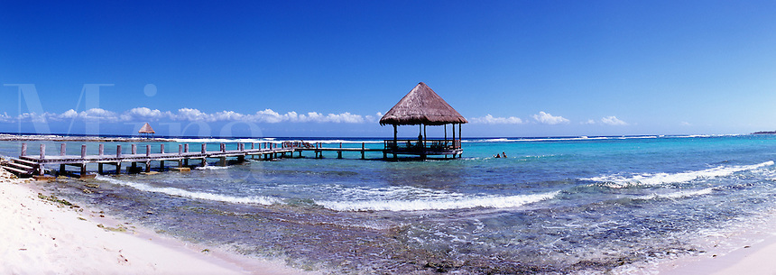 Mexico Quintana Roo Yucatan Peninsula Akumal Mayan Riviera pier with palapa jutting out to the water from the beach with surf