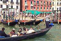 Gondolas with tourists in Venice harbor (Italy)
