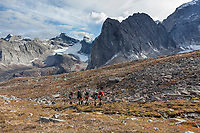Five backpackers trek along the mountains at the base of Arrigetch Creek, Arrigetch Peaks, Gates of the Arctic National Park, Alaska.