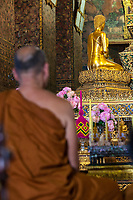 Bangkok, Thailand.  Buddhist Monk in front of Buddha at the Phra Ubosot, Wat Pho Temple Complex.