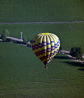 aerial photograph of a hot air balloon flying over vineyards in the Napa Valley, Napa County, California